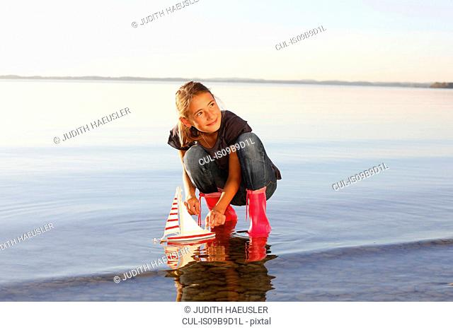 Young girl floating toy boat on water