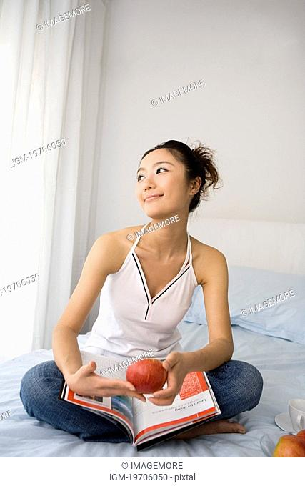 One young woman sitting on bed with magazine and apples