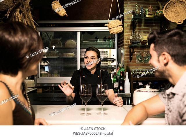Waitress talking to couple at bar with red wine glasses