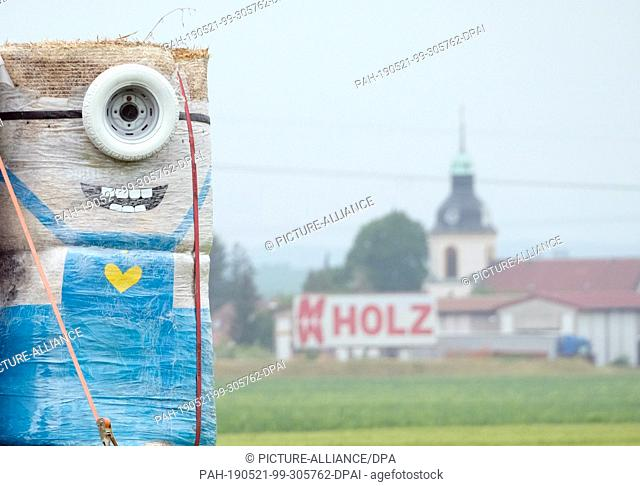 16 May 2019, Saxony, Liebschützberg: A minion figure made of straw bales, car wheels and other decorative material stands on a field on the Bundesstraße 6...