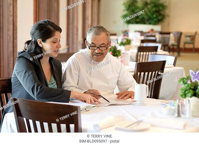 Hispanic business owner talking to restaurant chef
