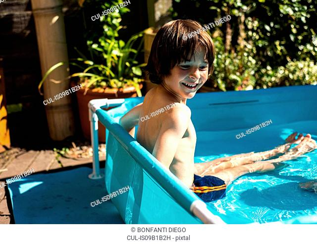 Happy boy playing in inflatable pool on summer day