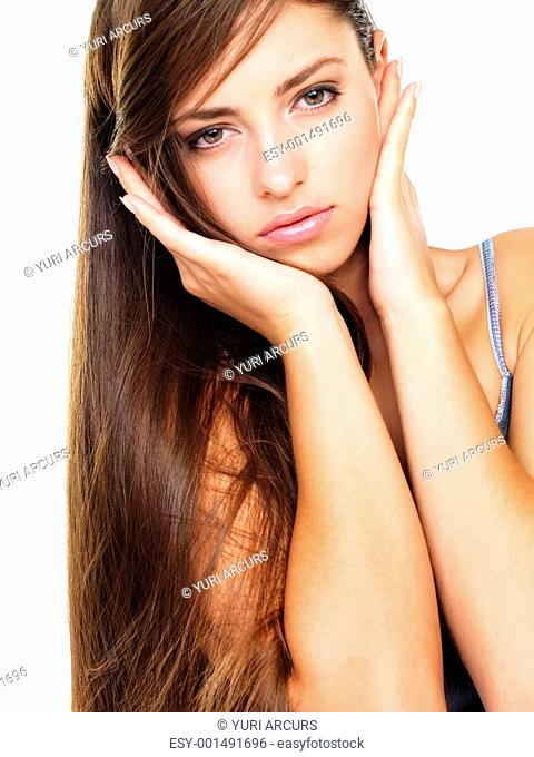 Serious long haired woman with hands on her cheeks over white background