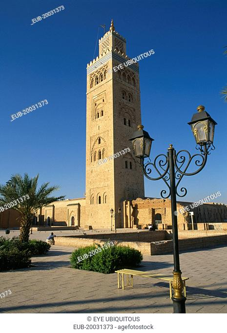 Koutoubia Mosque tower seen from pavement with blue sky behind and street lamps in foreground
