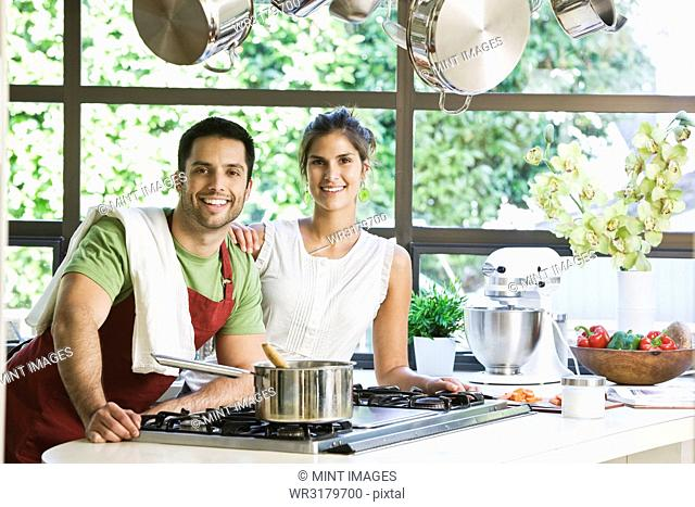 Hispanic couple at home in their kitchen cooking together