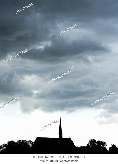 Bird flying over church and sky filled with storm clouds. Vadstena abbey, Sweden
