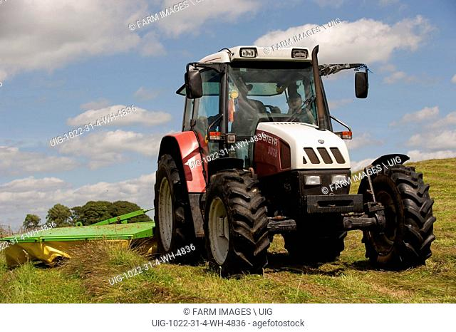 Farmer mowing meadow with drum mower using a Steyr 9078 tractor. (Photo by: Wayne Hutchinson/Farm Images/UIG)
