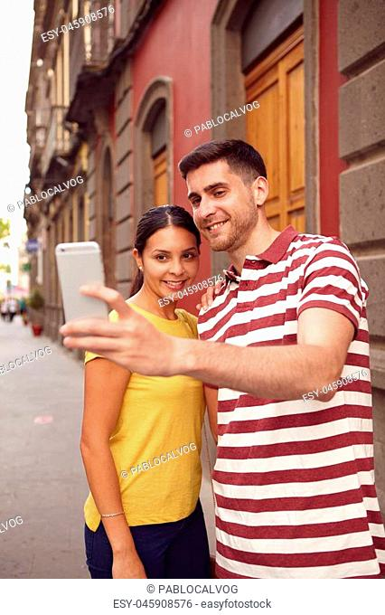 Young couple looking at cell phone while smiling joyously to take a selfie, dressed casually in t-shirts with old buildings behind them