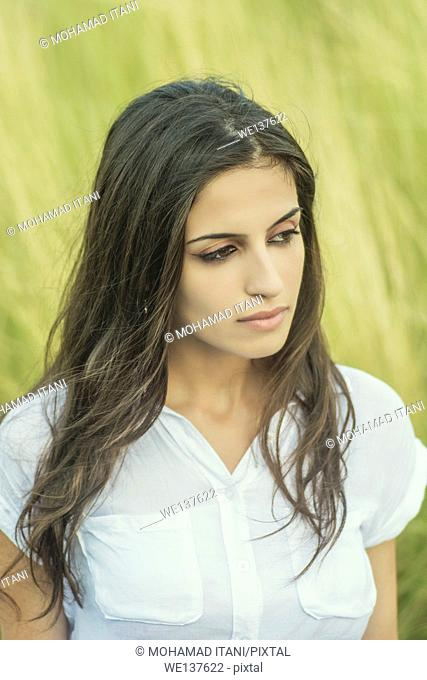 Serious young woman looking away outdoors