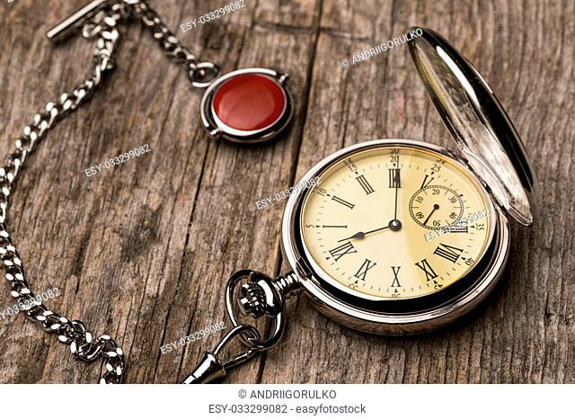 Old fashioned pocket watch with chain on rough wood background