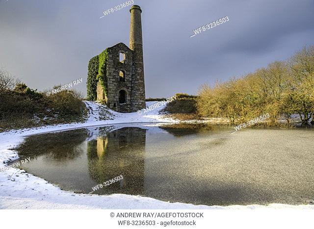 The Cornish engine house and pool on United Downs in Cornwall bathed in early morning light. The image was captured using a long exposure after a snowfall in...