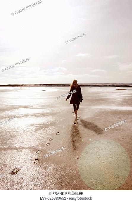 a holidaymaker walks in the wadden sea on the north coast