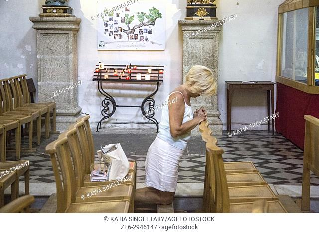 Older senior caucasian blond woman kneeling on the chairs on the church to pray. Her head is down, eyes close
