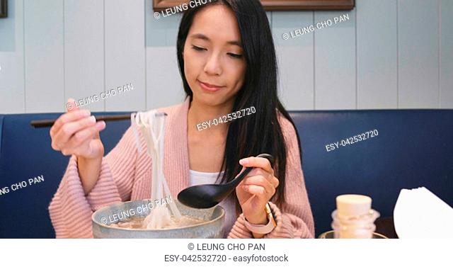 Woman eating noodles in restaurant