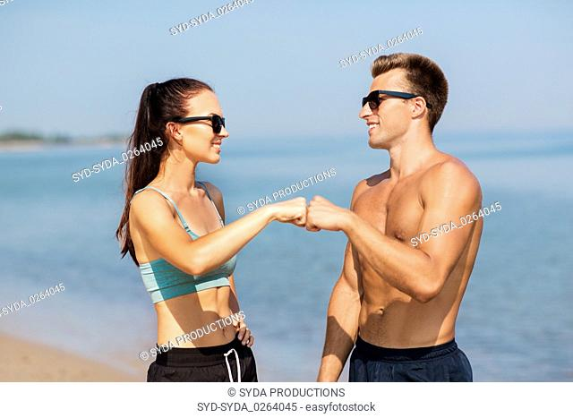happy couple in sports clothes and shades on beach