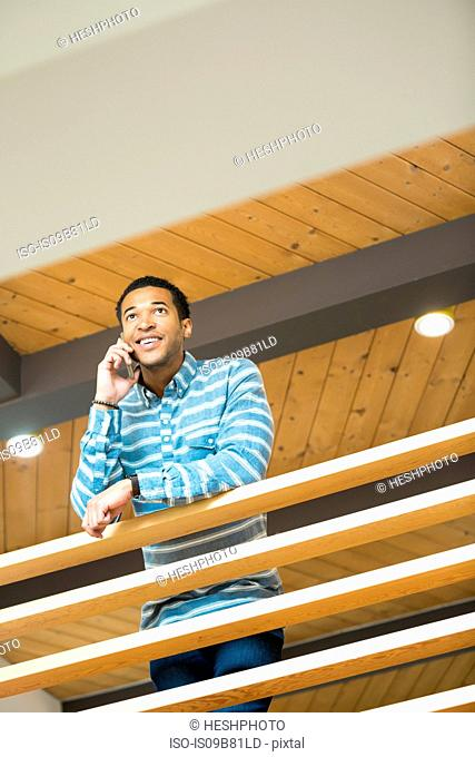 Young businessman on balcony making smartphone call