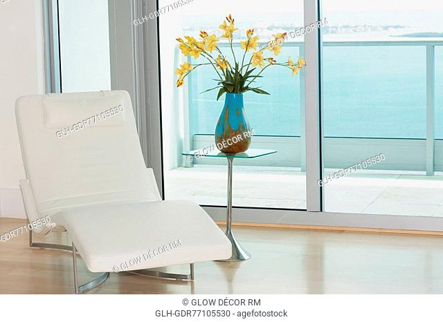 Reclining chair with a flower vase in a room