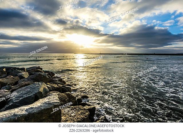 View of the ocean and sunbeams through the clouds with the Sun setting. Ocean Beach, San Diego, California, United States
