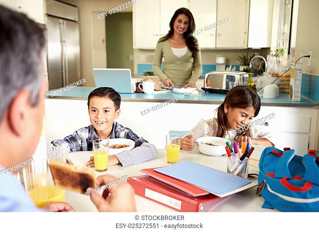 Hispanic Family Eating Breakfast At Home Before School