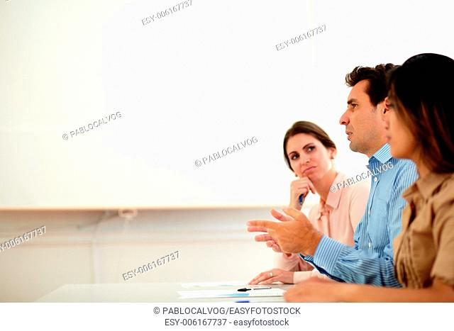Portrait of hispanic businessman on blue shirt speaking during a conference while sitting between two lady on office - copyspace