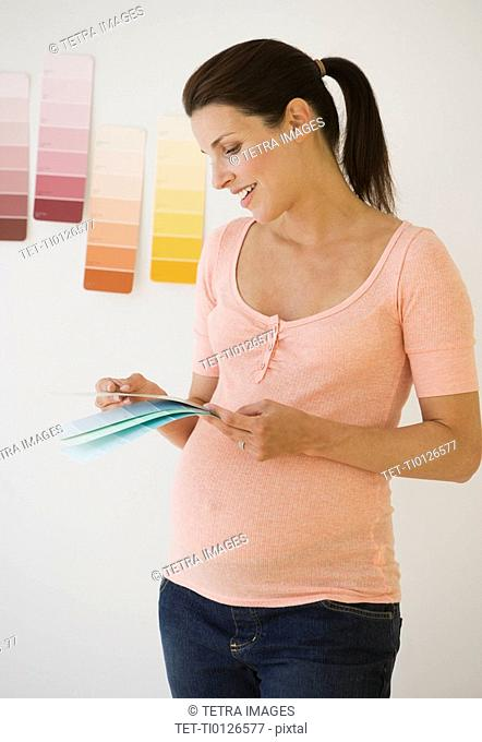 Pregnant woman looking at paint swatches