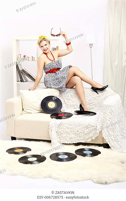 indoor portrait of beautiful happy young blonde size plus woman model sitting on sofa with vinyl records in interior
