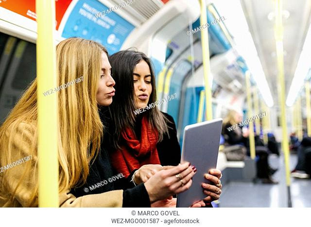 UK, London, Two young women in the underground using digital tablet