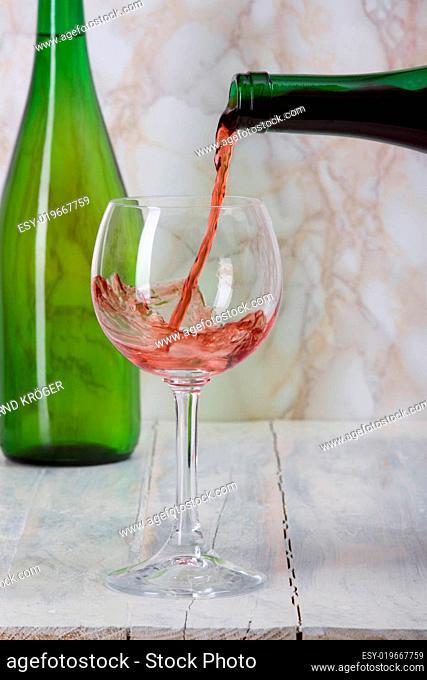Rotwein wird aus einer Flasche in ein Glas gegossen
