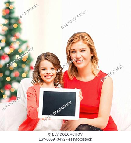 christmas, x-mas, winter, happiness, advertisement, modern technology concept - mother and daughter with tablet pc showing blank screen