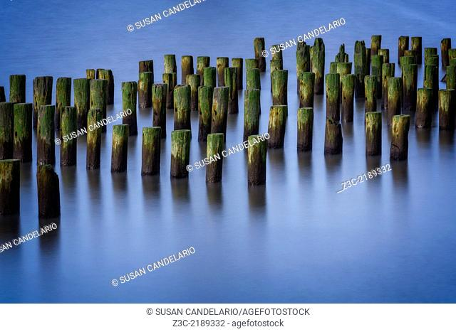 Tranquil waters with pilings at the Hudson River during the blue hour at sunset