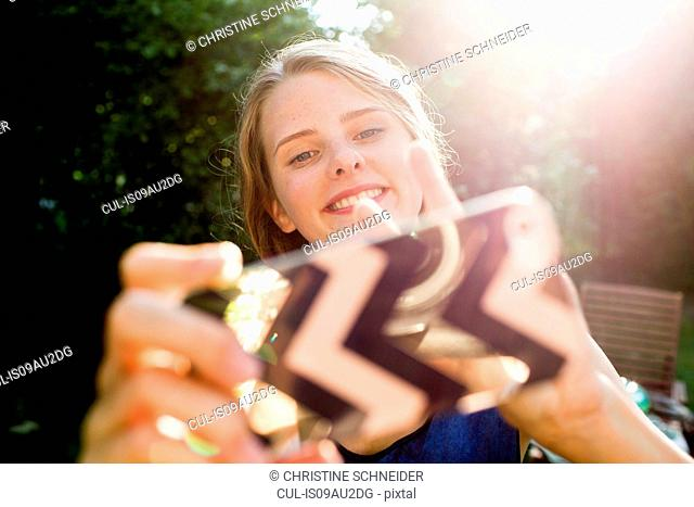 Teenage girl taking smartphone selfie in park