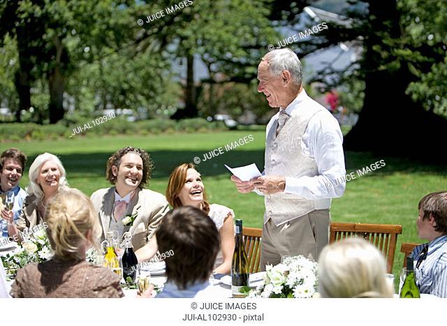 Senior man making a speech at a wedding reception