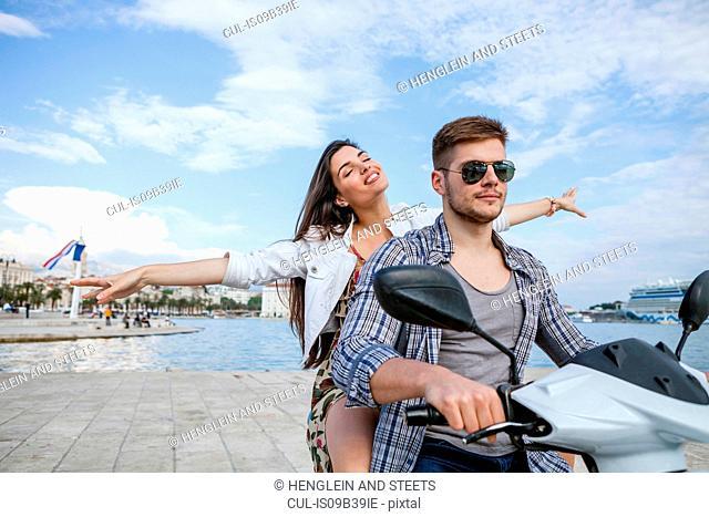 Young couple riding moped at harbour, Split, Dalmatia, Croatia