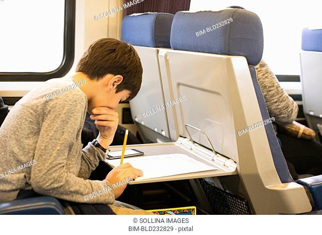 Mixed Race boy doing homework on train