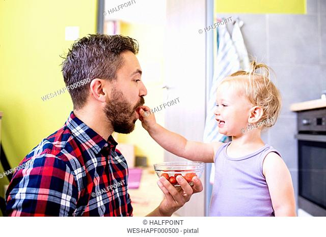 Father and daughter eating tomatoes in kitchen