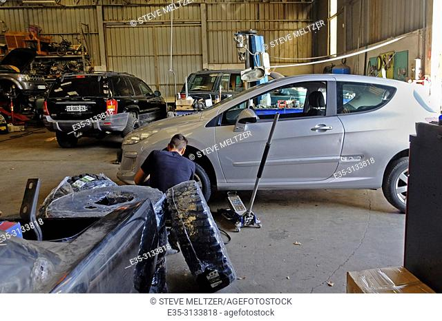 Changing a tire in an auto repair shop and garage in Pezenas, France