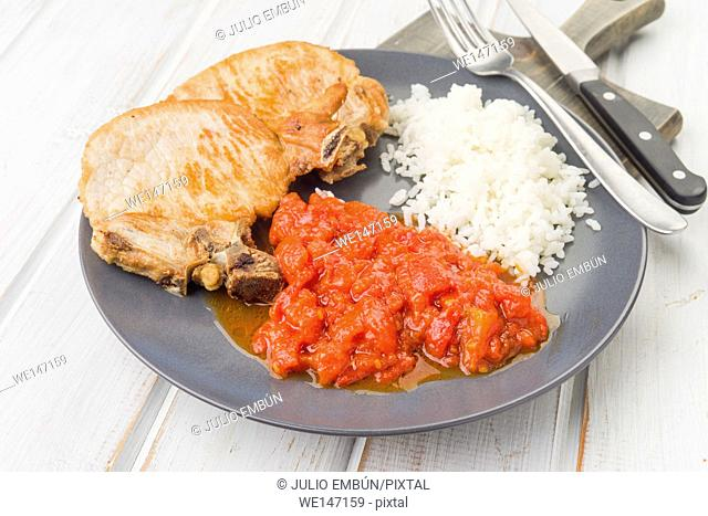 plate of pork chops with sauce and rice on wooden