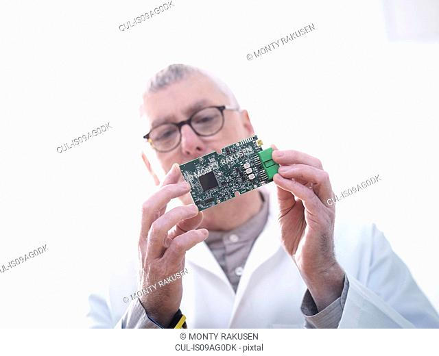 Engineer inspecting electronic circuitry for automotive use