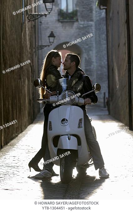 Couple embracing on a motor scooter