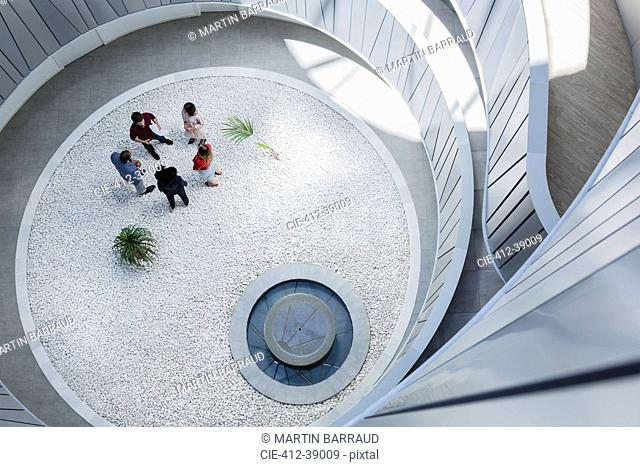 View from above business people talking in round modern office atrium courtyard