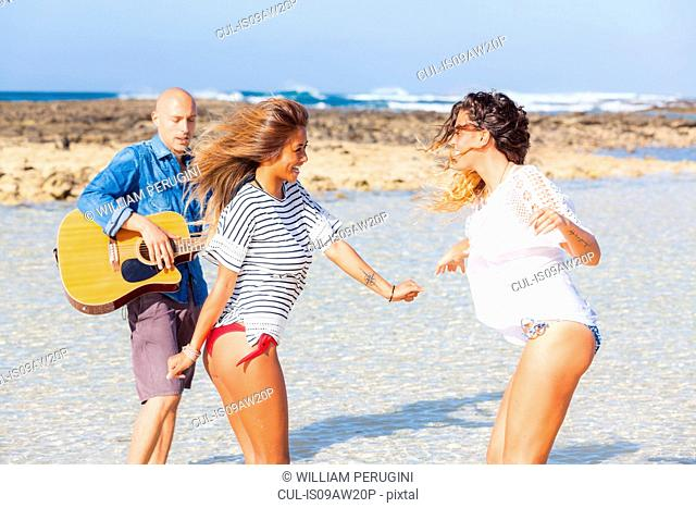 Man playing acoustic guitar and two young women dancing on beach, El Cotillo, Fuerteventura, Spain