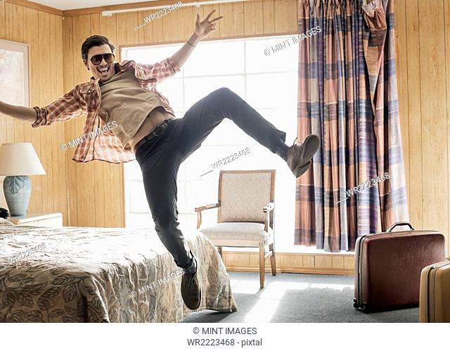A young man in sunglasses leaping in the air in a motel room