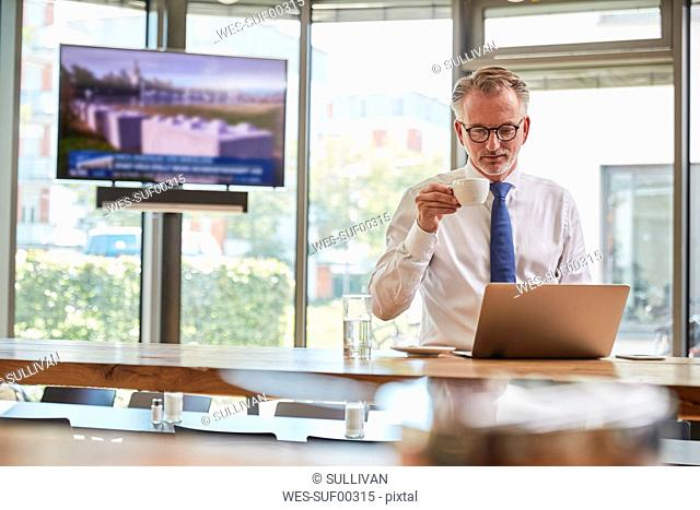 Businessman waiting at the airport, using laptop and drinking coffee