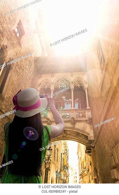 Rear view of woman taking photo of barrio gotico, Barcelona, Catalonia, Spain, Europe