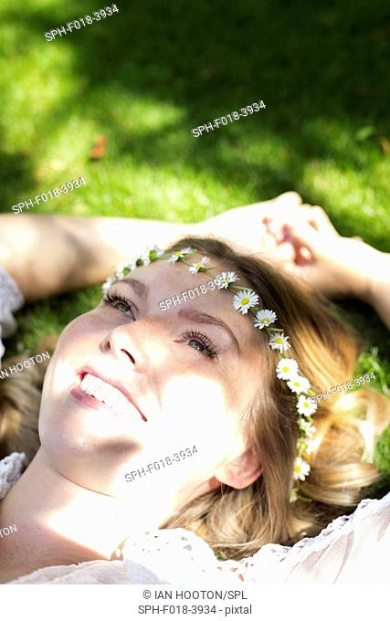 MODEL RELEASED. Young woman lying on grass wearing daisy chain