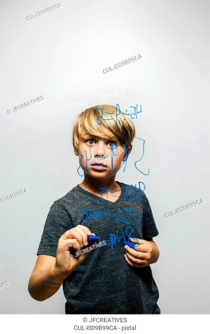 Boy holding blue marker pen staring at equation on glass wall