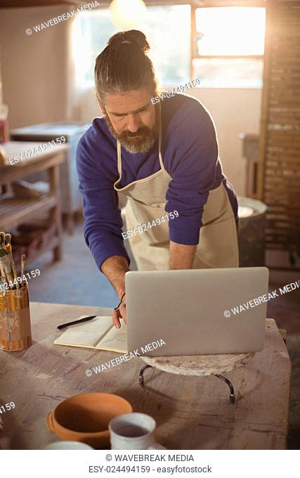 Male potter working on laptop