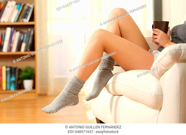 Side view of a waxed woman legs wearing socks sitting on a sofa in the living room of a house interior
