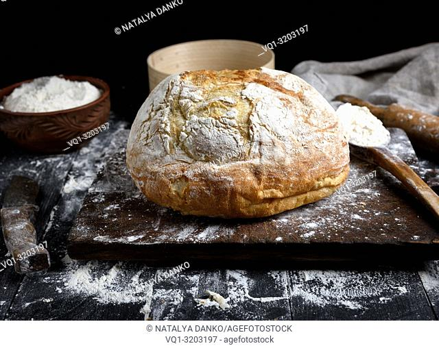 baked round white wheat bread on a brown wooden board and ingredients