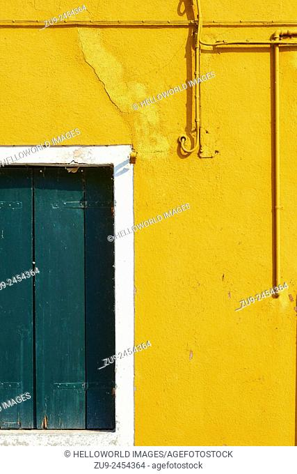 Yellow wall with pipes, wires and green shutters, Burano, Venetian Lagoon, Veneto, Italy, Europe